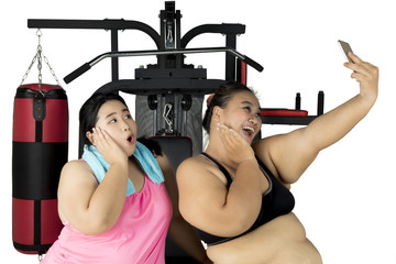 Fat women taking selfie in the center gym