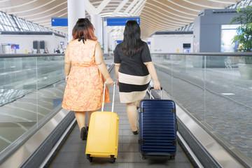 Fat women walking on the escalator airport
