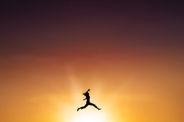 Joyful woman leaps at dusk time