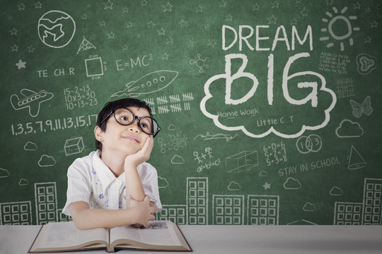 Little girl looking at dream big text