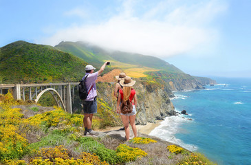 Family looking at beautiful summer mountains landscape, on hiking trip. Father taking photos with  phone.   Bixby Bridge,  on highway 1 in California over Pacific Ocean. Big Sur, California, USA