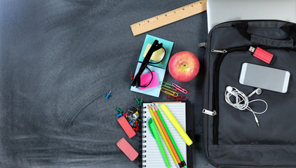 Back to school concept with modern technology and traditional objects on erased chalkboard background