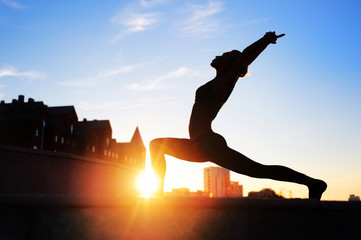 silhouette of a woman in warrior yoga  pose at the sundown background
