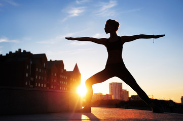 silhouette of a woman practicing warrior yoga  pose at the evening city background