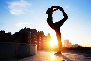 Woman practicing one leg standing yoga pose at the city sundown background