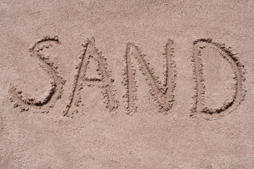 "Handwritten word ""SAND"" on brown sand on the beach in sunny day"