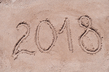 "Handwritten digits ""2018"" on brown sand on the beach in sunny day"