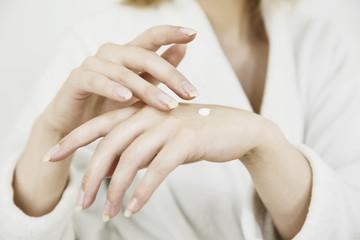 Junge Frau beim eincremen der Hände