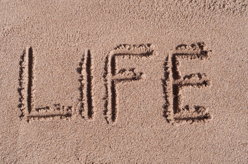 "Handwritten word ""LIFE"" on brown sand on the beach in sunny day"