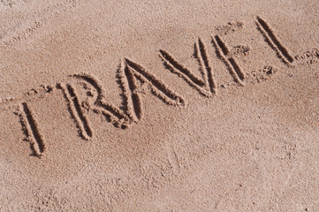 "Handwritten word ""TRAVEL"" on brown sand on the beach in sunny day"