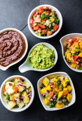 Traditional famous mexican sauces chocolate chili mole poblano, pico de gallo, avocado guacamole, salsa bandera, pinapple salsa, mango salsa on slate gray background