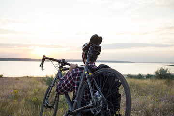 close up picture of man walking with bicycle and touring backpack, beautiful sunset in the lake
