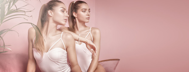 Beautiful caucasian twins female models on pink background.