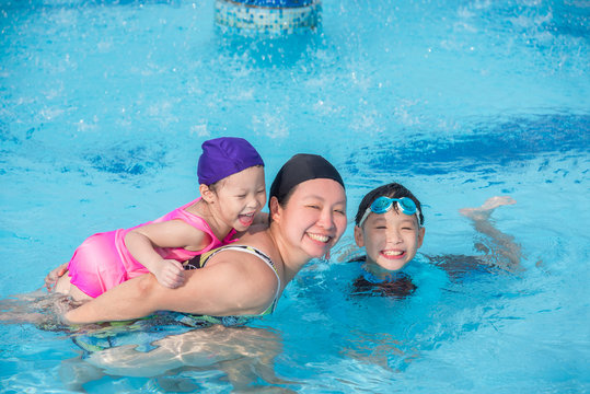 Asian mother and her childrean happy in swimming pool together