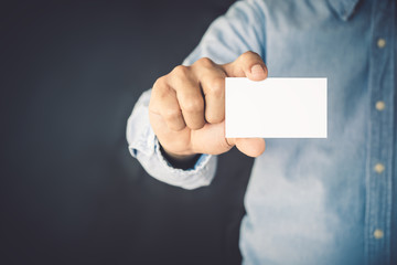 Young business man holding white business card on studio black background.