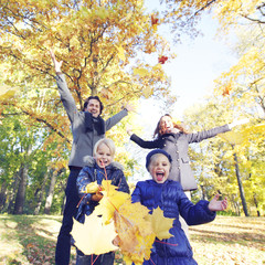 Happy family playing with autumn leaves