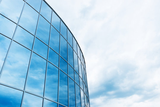 facade of modern glass blue office and sky with clouds reflected