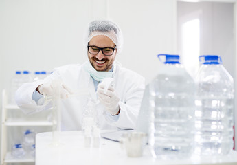 Happy lab scientist worker in glasses with laboratory pipettes.