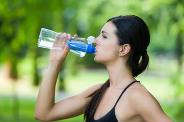 fitness woman drink water from bottle in a park in summer