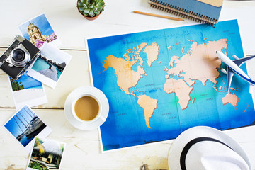 Traveller desk with folded paper map of world and photos