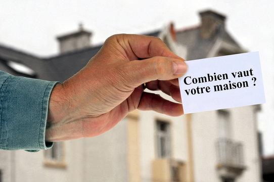 Homme tenant une carte avec combien vaut votre maison écrit dessus
