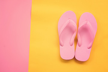 pink sandals on yellow and pink pastel background. Summer concept with copy space.