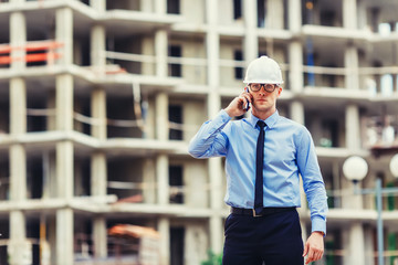 Construction engineer at the construction site looking at the camera and talking mobilephone