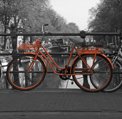 Black and white view of Amsterdam with orange bicycle