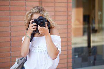 tourist girl taking photos on a street