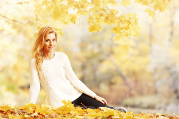 Woman sitting in autumn park