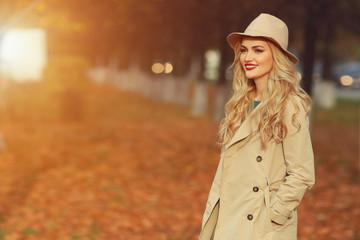 Beautiful elegant woman standing in fashionable beige hat in a park in autumn. Copyspace, sunlight