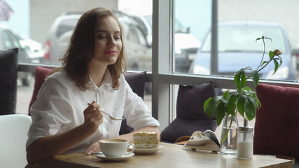 young beautiful female enjoys a fragrant coffee and sweet cake sitting in coffee house. Business woman resting during break