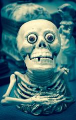 Funny greedy skeleton figurine at flea market in Paris (France). Death concept. Toned photo.