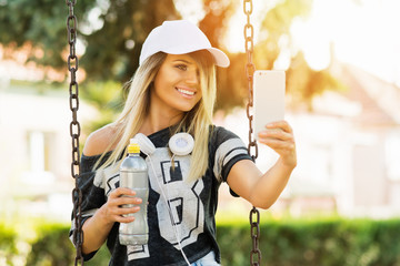 Sporty teenage girl with headphones on a swing in park taking a selfie on smart phone