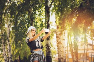 Sporty teenage girl taking a selfie on smart phone in park
