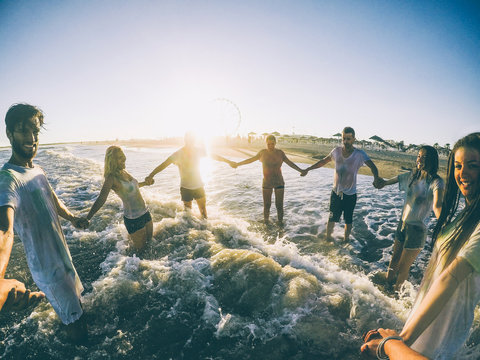 Pov view of happy friends having fun on the beach at sunset - Young people playing inside ocean in summer vacation - Friendship, youth,travel concept - Soft focus on right woman and left man faces