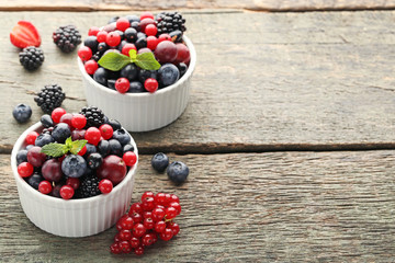 Ripe and sweet berries in bowls on wooden table