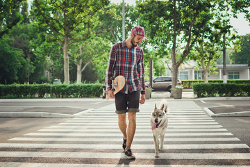 Young hipster man walking with skateboard and siberian husky dog on street road