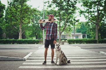 Young hipster man with skateboard and siberian husky dog standing on street road