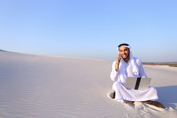 Successful Muslim male architect communicates on phone with clie