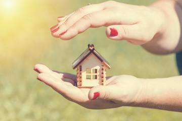 Female hands holding and saving small wooden house. Household concept. Toned.