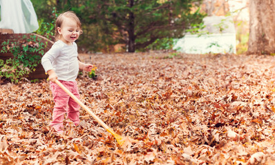 Happy toddler girl raking leaves