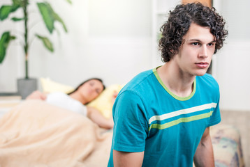Boyfriend is disappointed sitting on the bed while his girlfriend sleeps