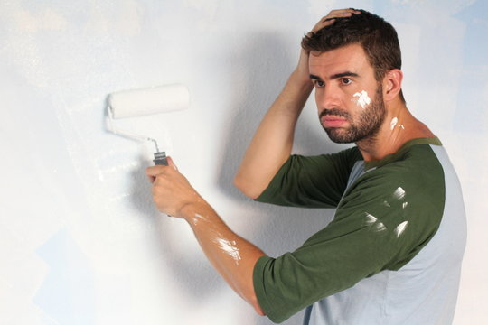 Exhausted man trying to paint a wall