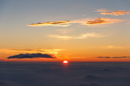 Sunrise above clouds and warm sky.