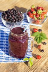 Strawberry, raspberry, blackberry and banana juice smoothie shake in glass mug, outdoors, close up