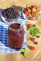 Strawberry, raspberry, blackberry and banana juice smoothie shake in glass mug, outdoors, close up