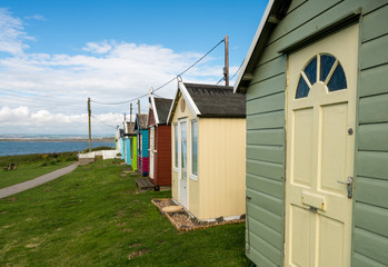 Colorful beach side huts on Devon coast of England
