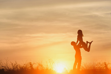Silhouette of  happy young couple in love hugging enjoys in summer , Loving man holding on hands his woman together outdoors