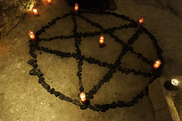 Satanic pentacle with candles in a dark ritual